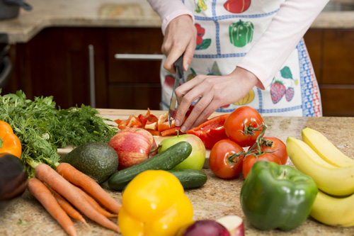 Woman wearing apron slicing a variety of colorful vegetables